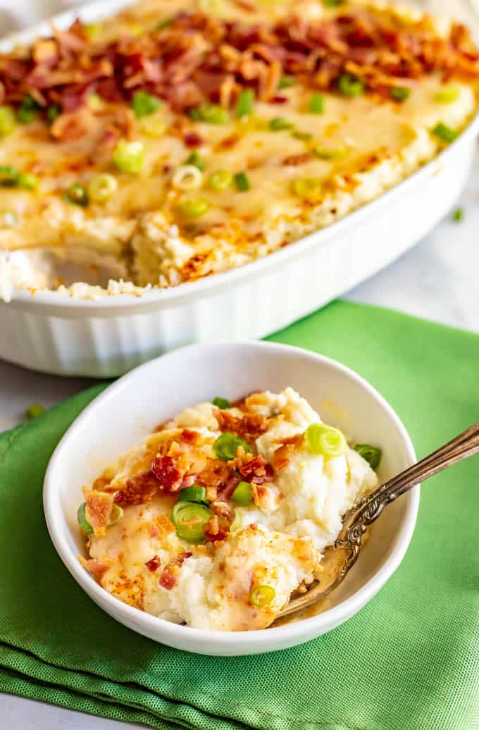 Mashed cauliflower casserole with cream cheese, cheddar cheese and bacon, served in a small white bowl