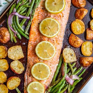 One-pan salmon and potatoes with green beans is an easy sheet pan dinner with wild-caught salmon, baby red potatoes and green beans, all roasted and topped with feta cheese and a lemony vinaigrette. #salmon #potatoes #sheetpan #easydinner #seafood