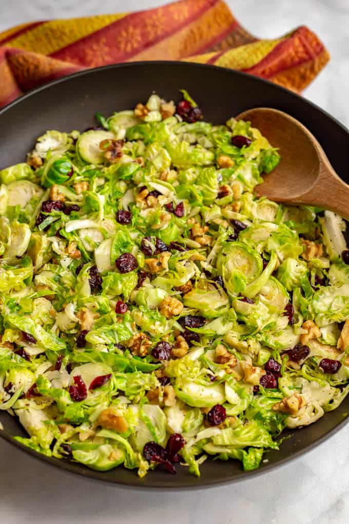 Shredded Brussels sprouts with dried cranberries and walnuts in a large sauté pan
