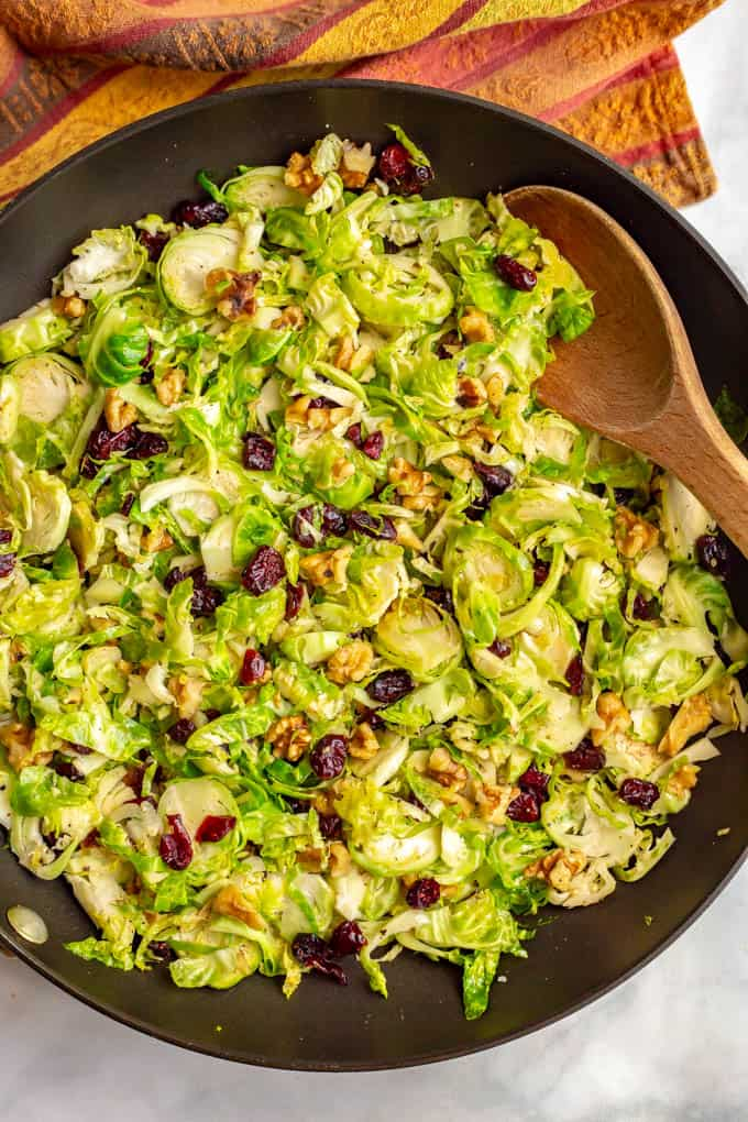 Shredded Brussels sprouts with cranberries and walnuts are a super quick and easy side dish with great flavors! It's perfect for the holidays or just a busy weeknight! #Brusselssprouts #sidedish #veggies #holidays #Thanksgiving #Christmas