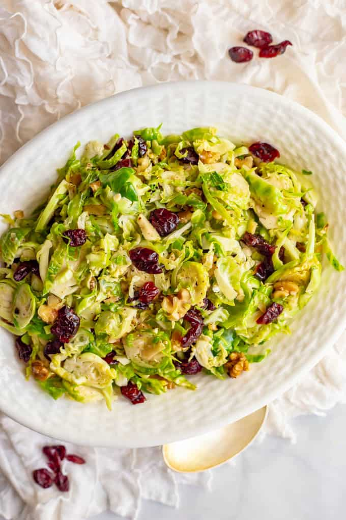 Shredded Brussels sprouts with dried cranberries and walnuts in a white serving dish with a serving spoon nearby