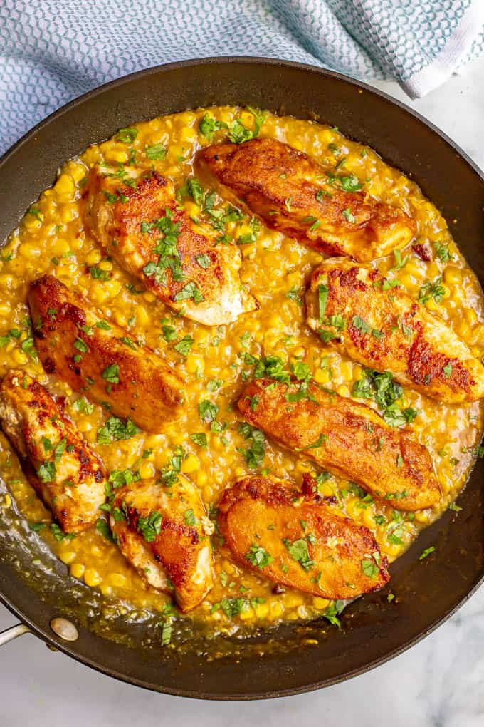 Skillet chicken with creamed corn in a large skillet with cilantro sprinkled on top