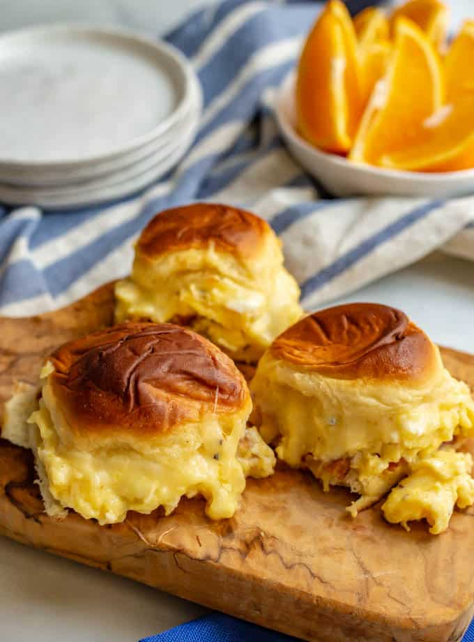 3 cheesy baked breakfast sliders served on a small cutting board with a bowl of oranges in the background