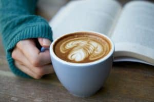 Coffee latte in a mug with a hand on handle and a book in the background