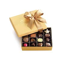 A gold box of chocolates with a gold bow on top