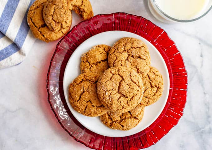 Overhead of old fashioned soft molasses cookies piled on a white plate with a red serving plate underneath