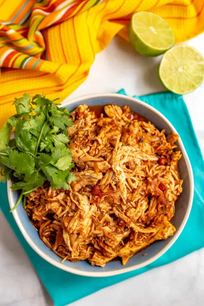 A bowl of crock pot Mexican shredded chicken with cilantro on the side and a cut lime on the table