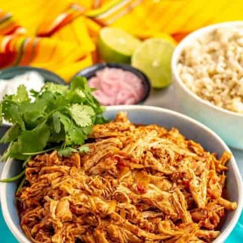 Slow cooker Mexican shredded chicken is just 3 easy ingredients and minutes to prep, but has such delicious flavor! Use it for tacos, nachos, grain bowls, sliders, salads and more! #slowcooker #shreddedchicken #easychickenrecipes #crockpot #mexicanchicken