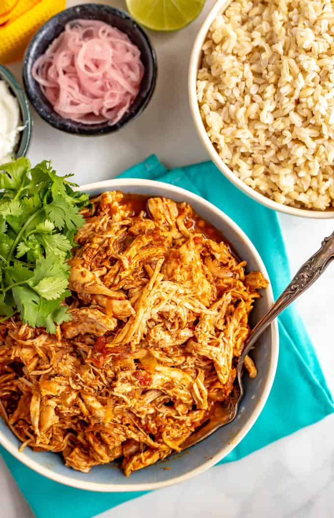 Shredded Mexican chicken in a bowl with cilantro and sides of rice, pickled red onions and sour cream