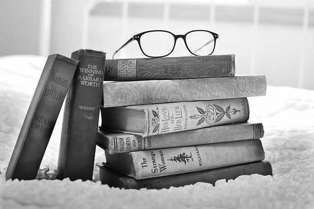 Black and white photo of a stack of books with glasses perched on top