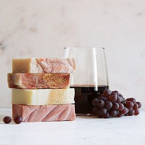 Uncommon Goods wine soaps with a glass of wine and red grapes