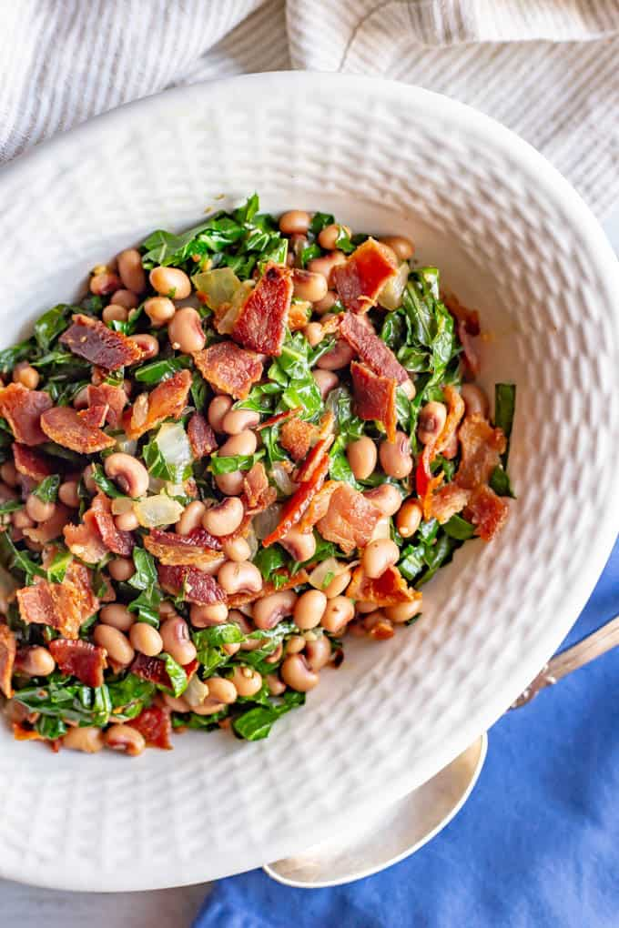 Overhead photo of collard greens and beans topped with bacon in a white serving dish