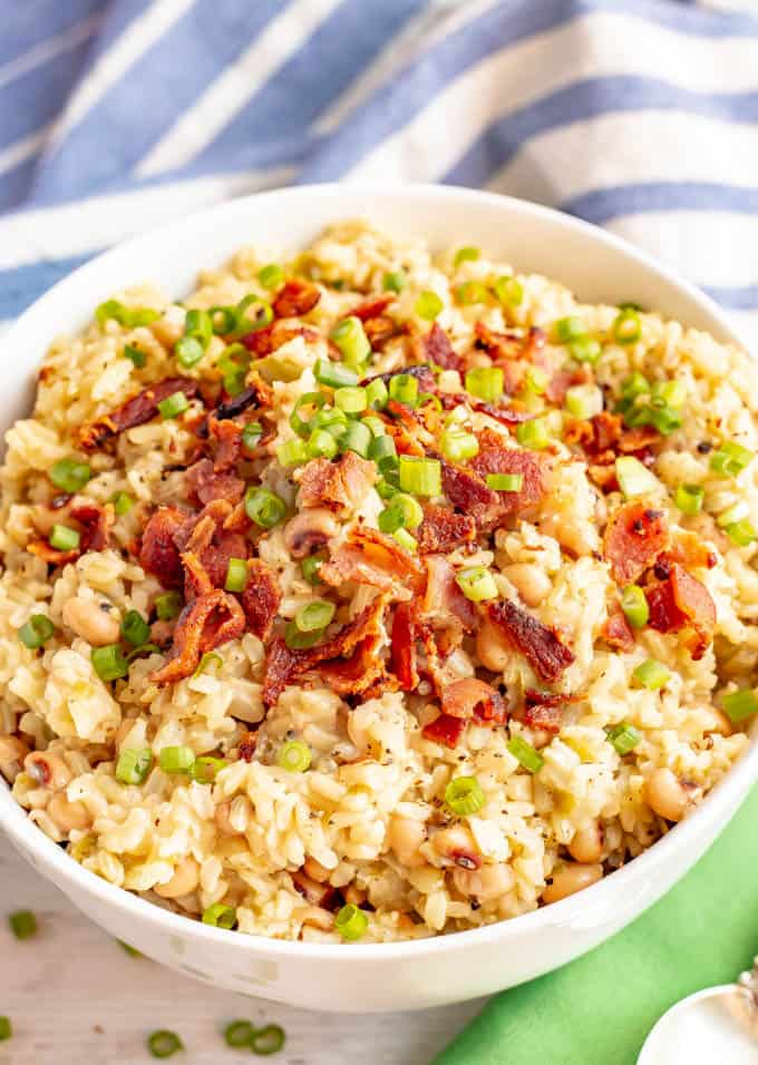 Easy one-pot Hoppin' John topped with bacon and green onions in a white serving bowl