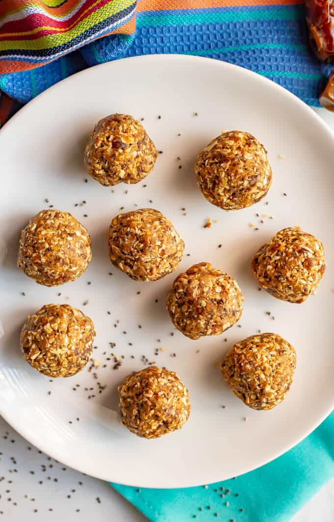 Healthy peanut butter energy balls on a white plate with a sprinkling of chia seeds and napkins underneath