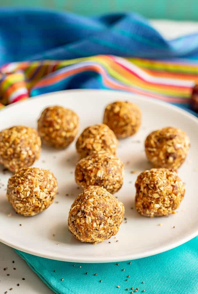 Healthy peanut butter energy balls arranged on a white plate with a turquoise napkin underneath