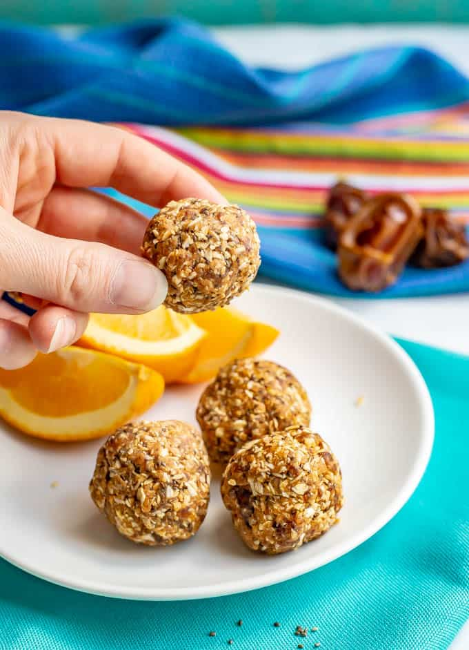 Healthy peanut butter energy balls on a white plate with sliced oranges and one being held up