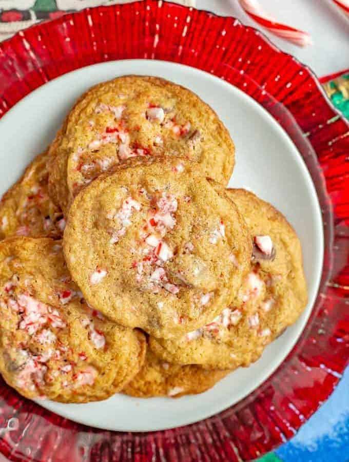 Peppermint chocolate chip cookies piled on a white plate with a red plate underneath and candy canes to the side
