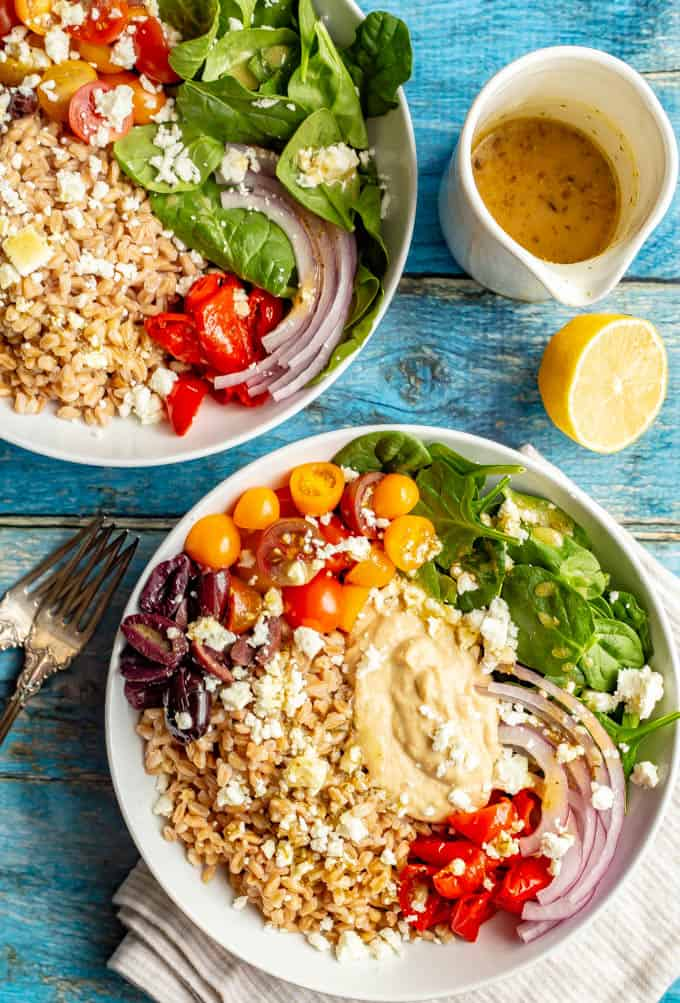Loaded Greek grain bowls with farro, hummus, tomatoes, spinach, peppers, olives, red onion and feta cheese