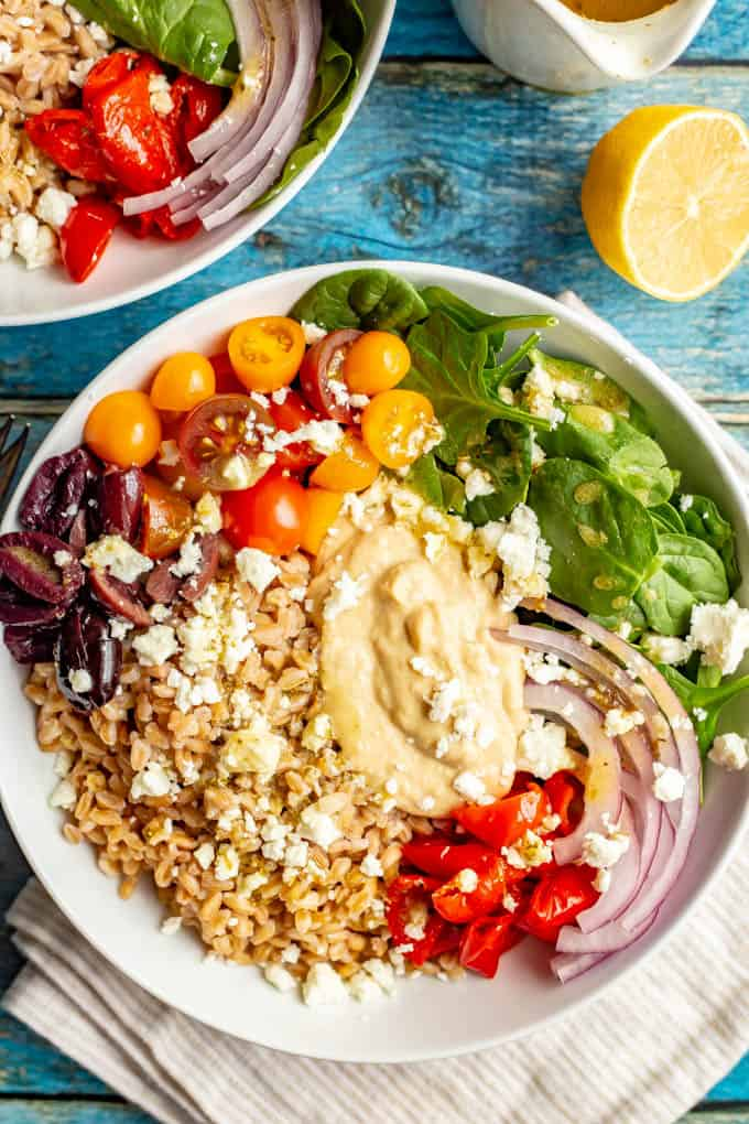 Vegetarian Greek grain bowls are loaded with wholesome grains and veggies and topped with an easy red wine vinaigrette for a beautiful and delicious lunch or light dinner! #grainbowl #mealprep #vegetarian #lunchideas #mediterraneanfood
