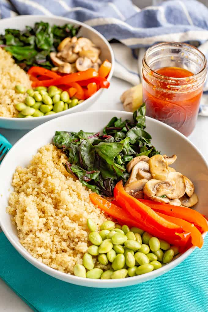 Asian quinoa power bowls with greens, mushrooms, peppers and edamame with napkins and soy ginger dressing laid out