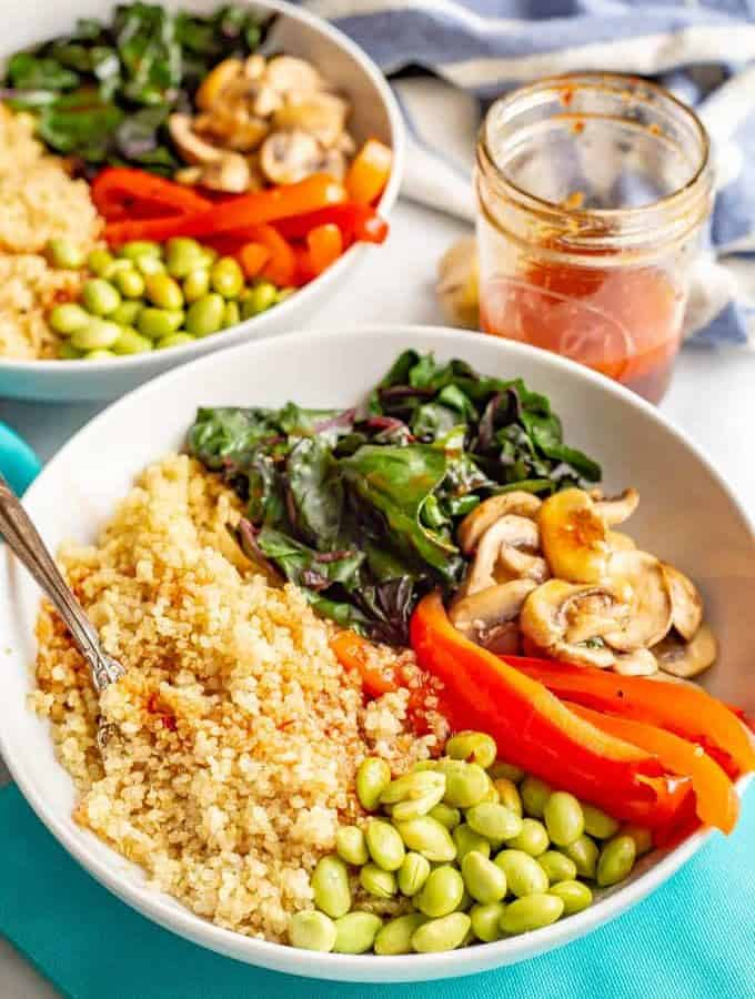 Warm Asian quinoa power bowls are full of wholesome, colorful and delicious veggies and finished off with an easy, but addictive, soy ginger dressing. Vegan, gluten-free and dairy-free. #veganrecipes #meatlessMonday #vegetariandinner #quinoa #quinoabowl