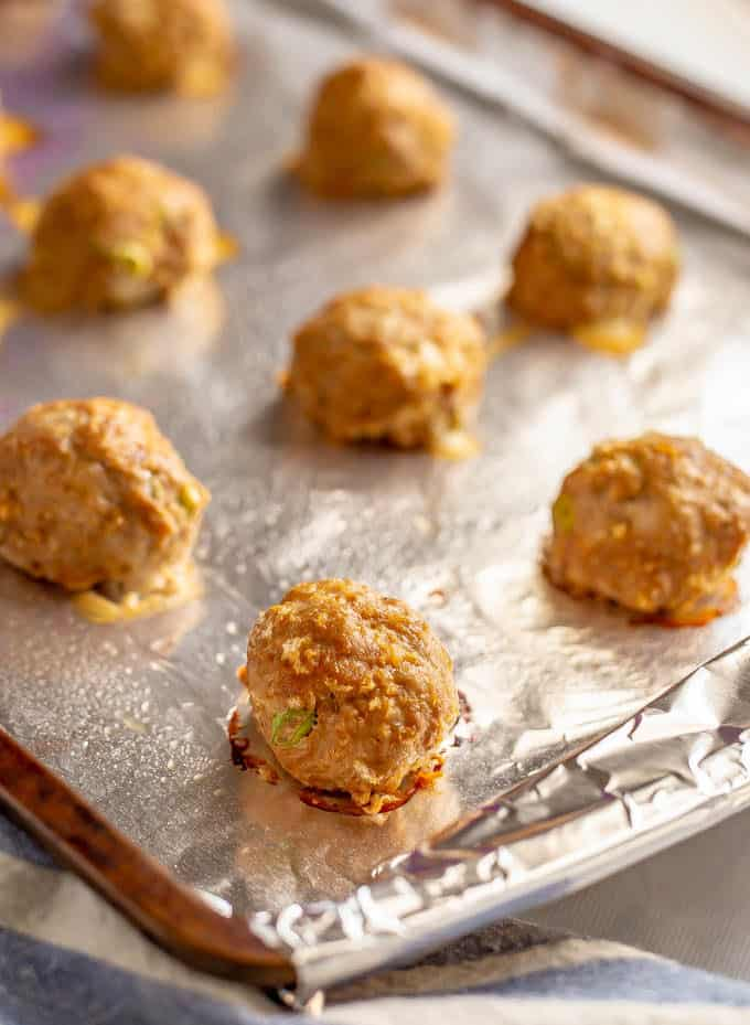 Baked Asian style meatballs on a baking sheet lined with aluminum foil