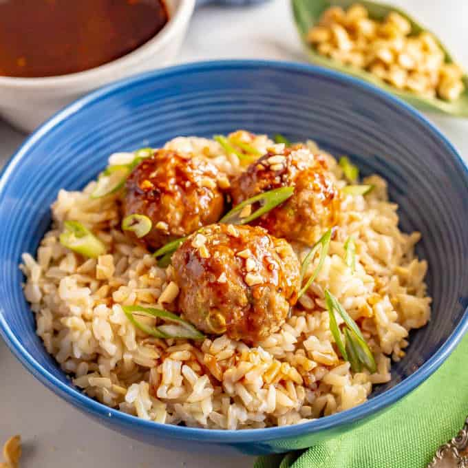 Baked Asian turkey meatballs served on a bed of brown rice with green onions and peanuts sprinkled on top