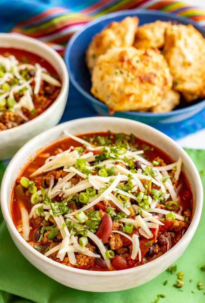 Bowl of Super Bowl chili with toppings and a cheddar biscuits in a separate bowl nearby