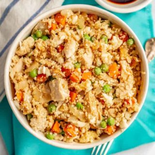 Cauliflower fried rice with chicken, peas and carrots in a white bowl on a turquoise napkin