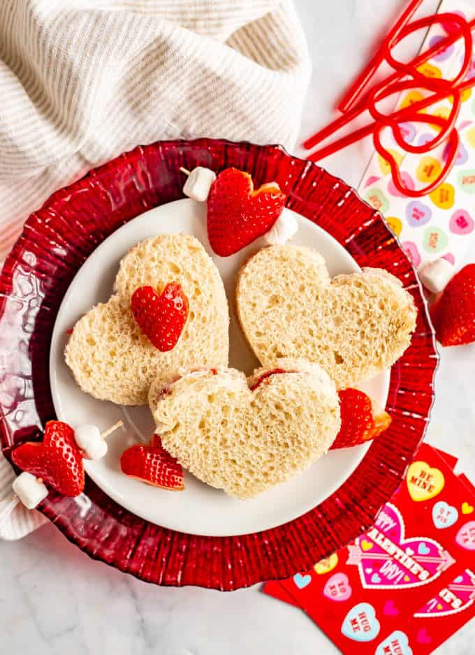 Heart shaped sandwiches with cream cheese and strawberry jam and Valentine's Day decorations