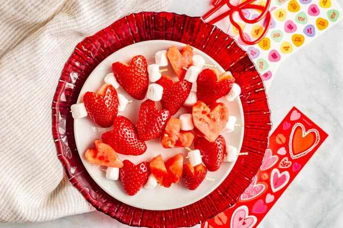 A plate full of heart-shaped strawberry and watermelon pieces on kabobs with mini marshmallows
