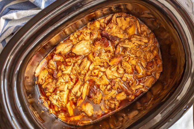 Slow cooker honey garlic chicken in a crock pot with lots of sauce