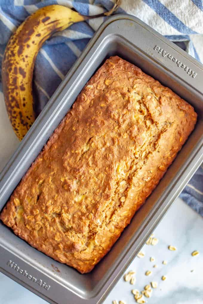 A baked loaf of whole grain applesauce banana bread in a loaf pan