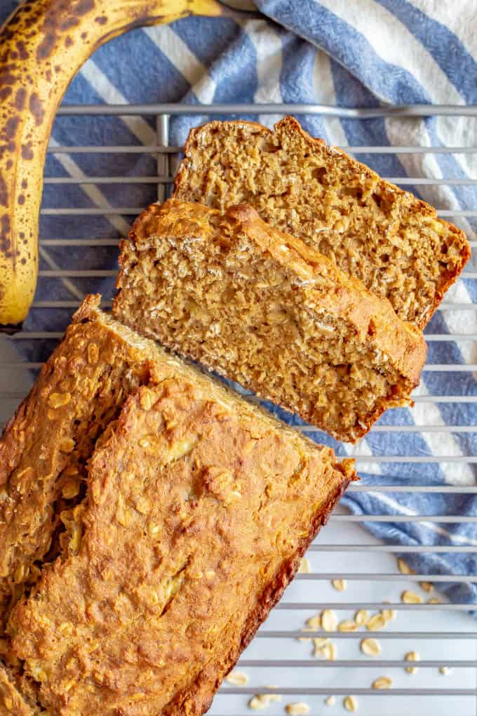 A loaf of whole grain banana applesauce bread partially sliced and cooling on a baking rack