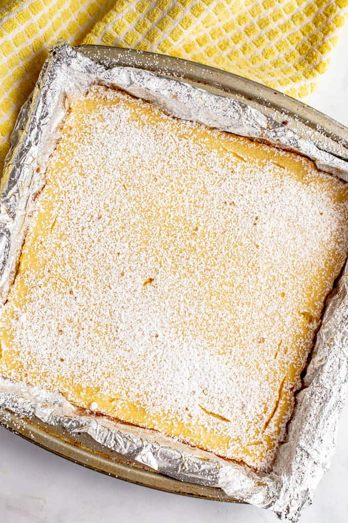 Healthy lemon bars baked in a baking dish and dusted with powdered sugar