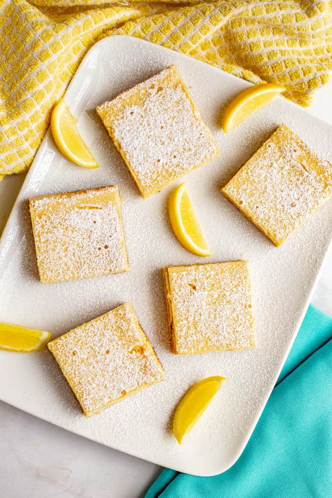 Healthy lemon squares served on a white plate and dusted with powdered sugar
