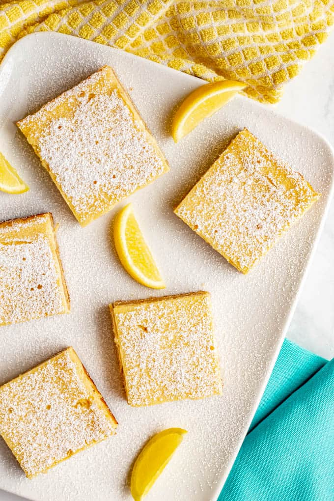 Healthier lemon bars have a shortbread crust and a silky smooth slightly sweet, slightly tart creamy lemon filling on top. These bars are whole wheat and naturally sweetened - and just 7 ingredients! #lemonbars #lemonsquares #lemon #dessert