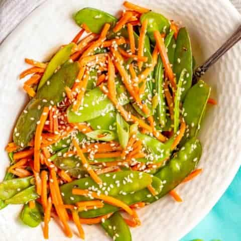 Sesame snow peas and carrots is a quick and easy side dish that's ready in just 10 minutes! You'll love how colorful and tasty this recipe is for a quick weeknight veggie side! #snowpeas #carrots #sidedish #easysides #glutenfreerecipes