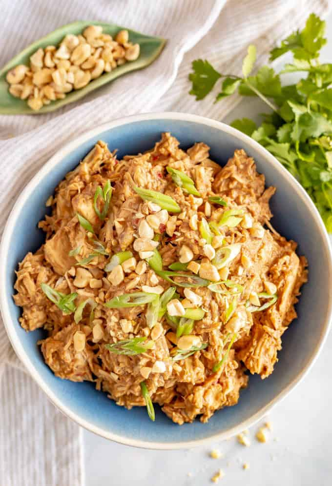 Slow cooker peanut chicken served in a blue bowl with chopped peanuts and sliced green onions