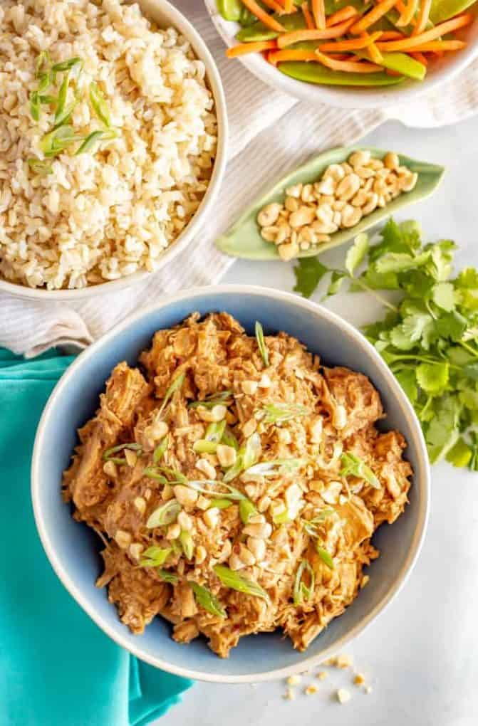 Slow cooker peanut chicken served family style with bowls of brown rice and veggies nearby