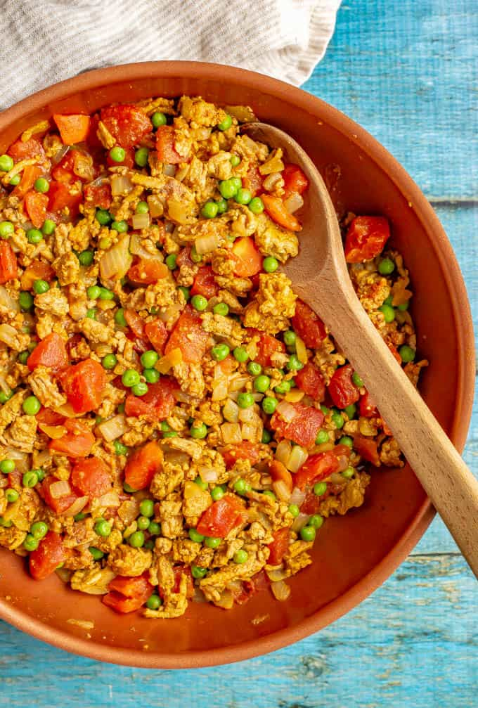 Curry turkey and peas with tomatoes cooked in a large skillet