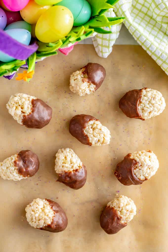 A collection of chocolate dipped Easter Rice Krispie treats on wax paper with an Easter basket
