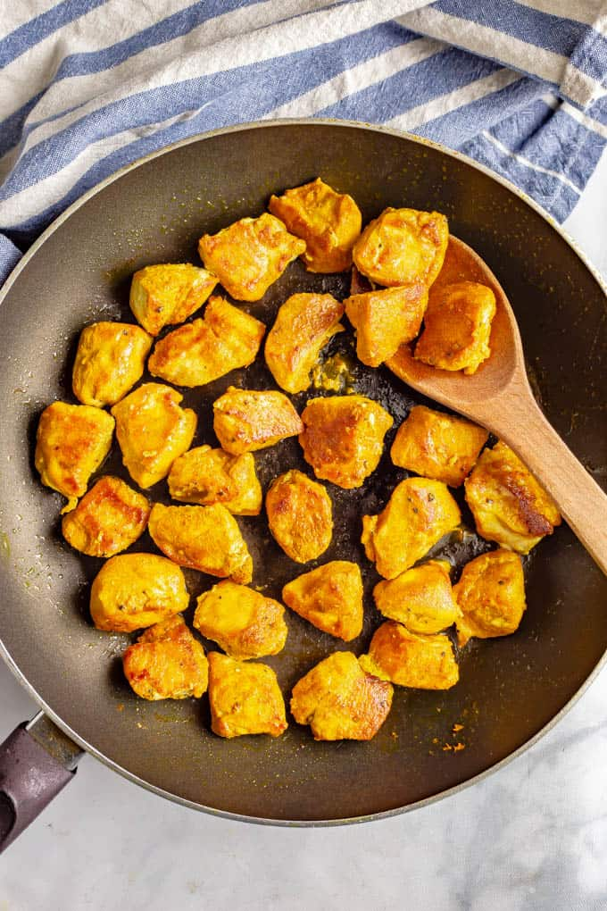 Cubes of chicken cooked in a skillet with turmeric and spices