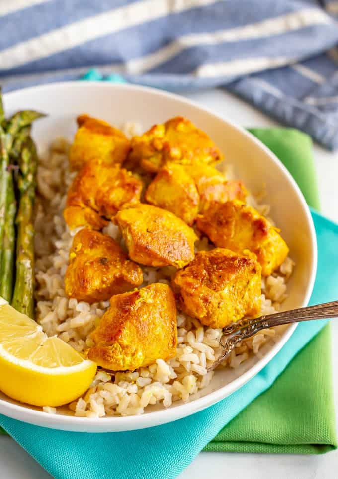 Easy turmeric spiced chicken pieces served over steamed rice with asparagus