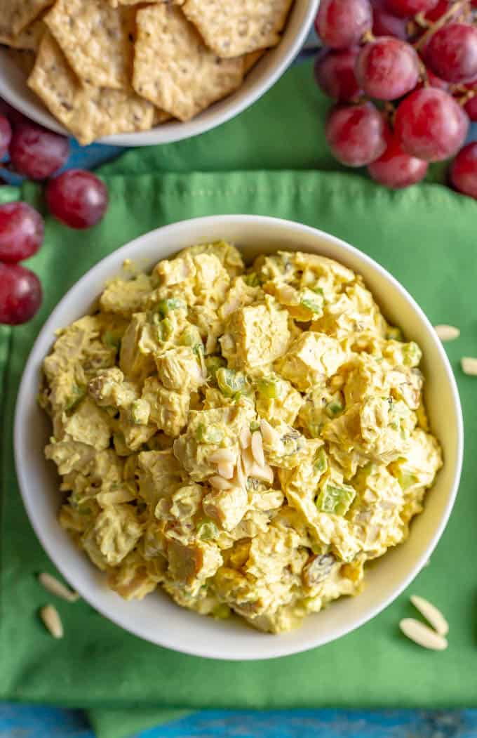 Healthy curried chicken salad in a white bowl with red grapes and crackers nearby