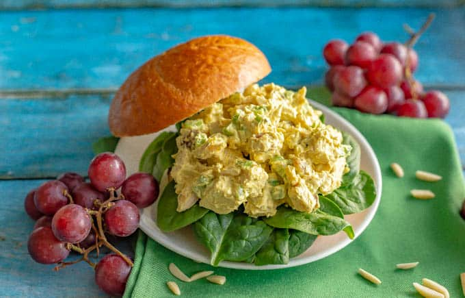 Curry chicken salad served as a sandwich on a bun with red grapes alongside