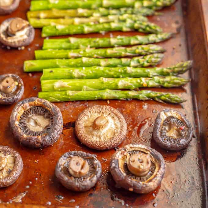 Asparagus and wild mushrooms on a baking tray after being roasted in the oven