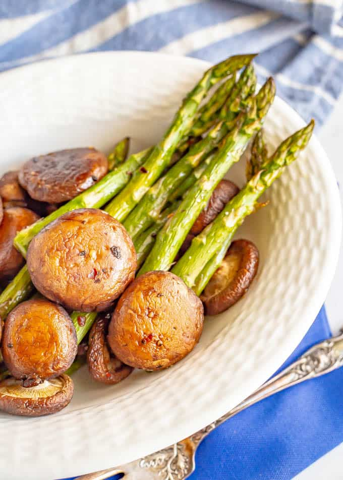 Roasted mushrooms and asparagus served in a white serving bowl