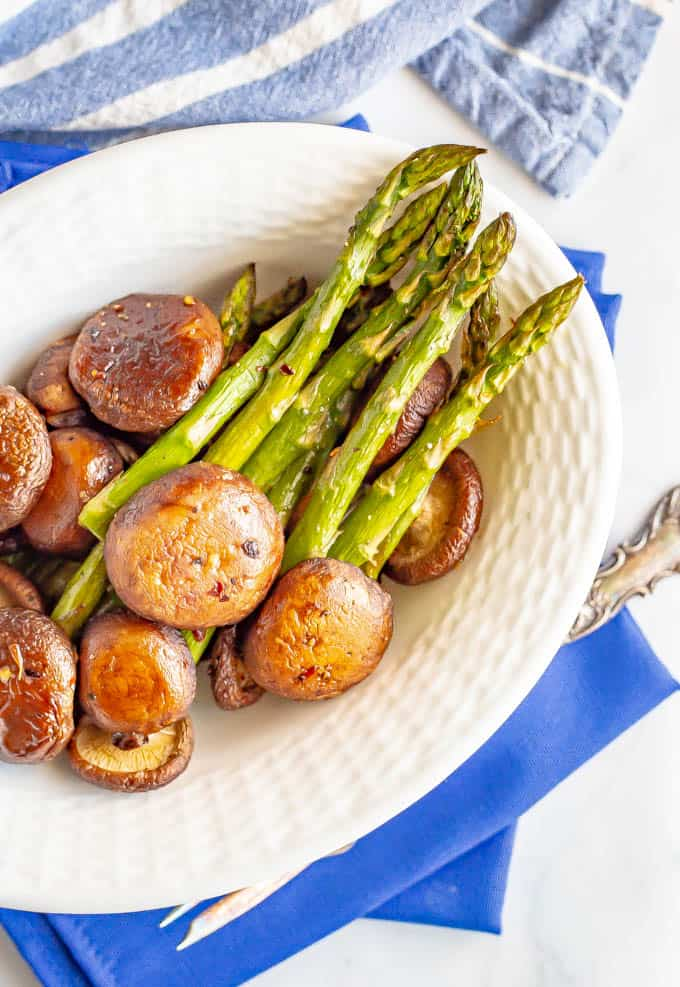 Cooked asparagus and mushrooms veggie side dish served in a white dish