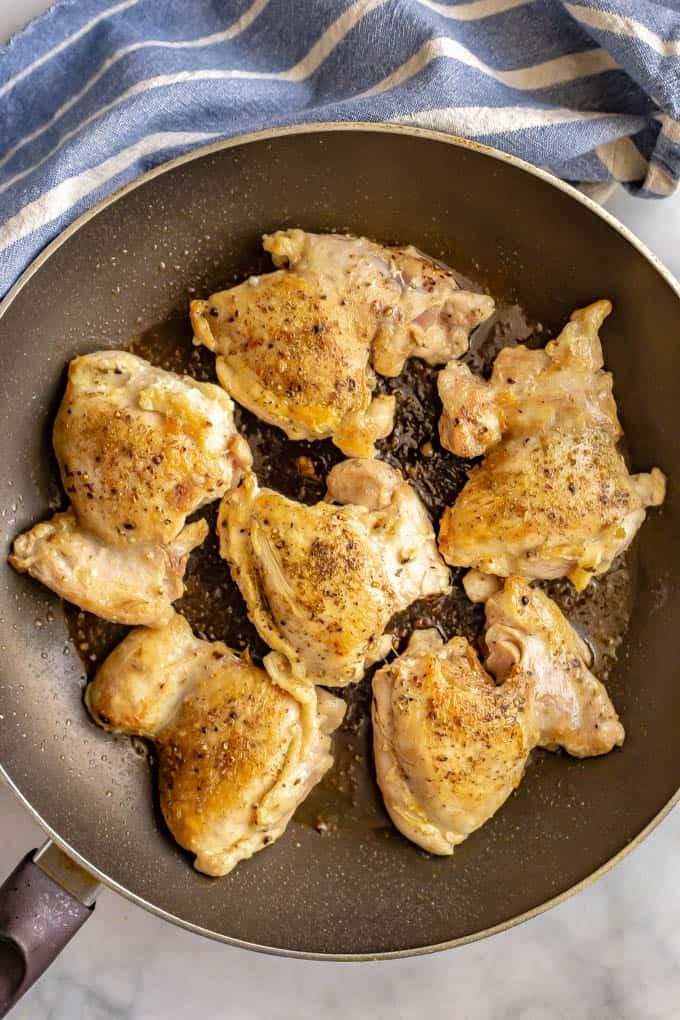 Chicken thighs seared in a large pan